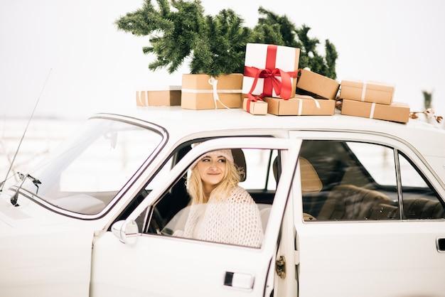 Het meisje rijdt in een retro-auto versierd met een kerstboom en presenteert in een besneeuwd bos. het concept van een winter kerst fotoshoot