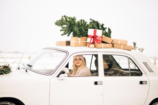 Het meisje rijdt in een retro-auto versierd met een kerstboom en presenteert
