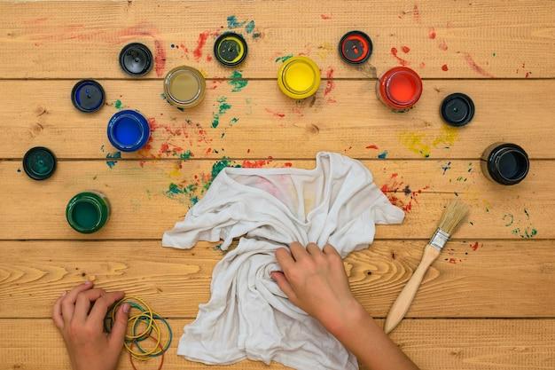 Het meisje rolt een wit t-shirt op om te schilderen in de stijl van tie-dye