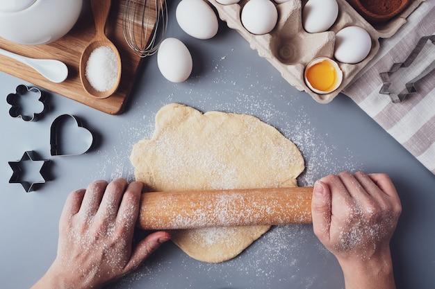 Het meisje rolt het deeg uit met een houten deegroller voor het maken van cupcakes of koekjes. platte compositie met keukengerei en ingrediënten, kopieer ruimte. concept van bakken voor de vakantie.