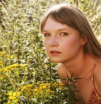 Het meisje ruikt gele bloemen op het gebied
