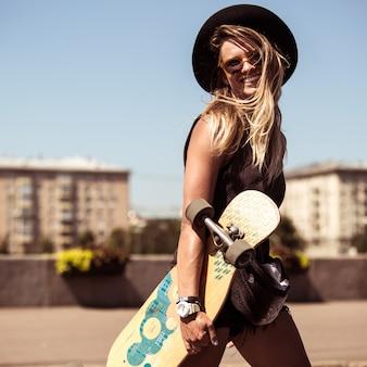 Het meisje schaatst op skateboard