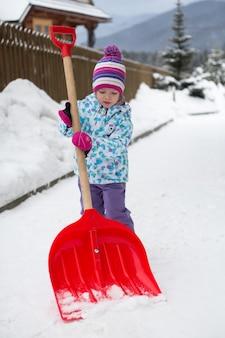 Het meisje schept de sneeuw in de tuin
