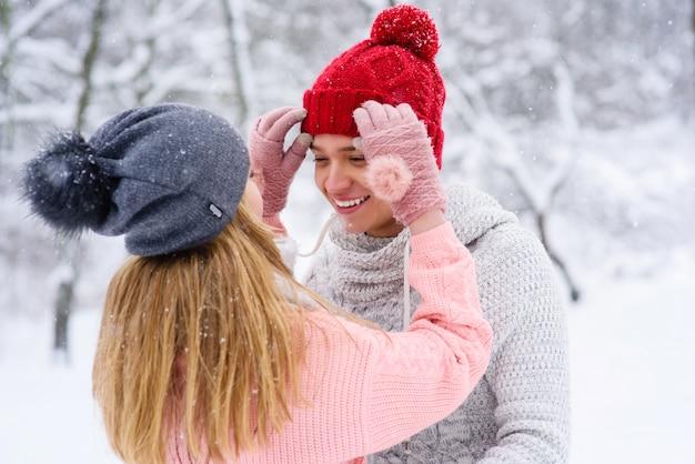 Het meisje schikt hoed van haar geliefde vriend