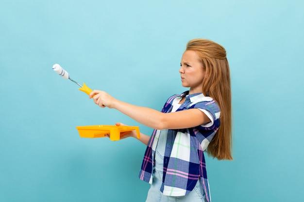 Het meisje schildert een lichtblauwe muur