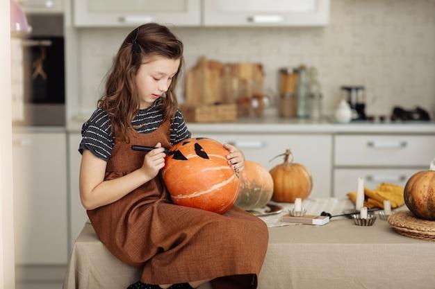 Het meisje schildert een pompoen voor halloween-voorbereiding voor halloween