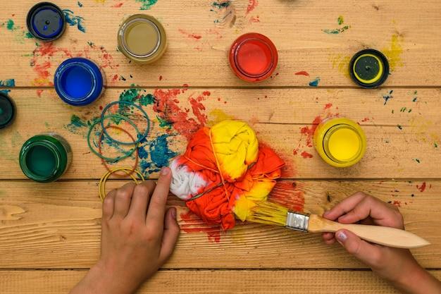 Het meisje schildert een t-shirt in de stijl van tie-dye. kleurstof in tie-dye-stijl.