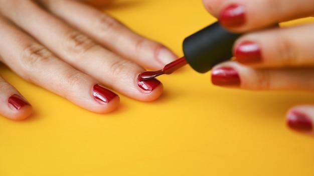 Het meisje schildert haar nagels met rode vernis.
