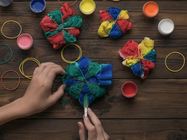 Het meisje schildert kleding in de stijl van tie dye in donkere kleuren. stof beitsen in tie-dye-stijl.
