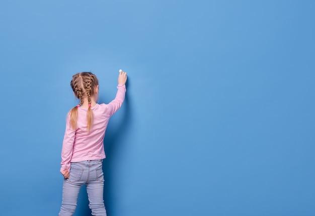 Het meisje schrijft met krijt op blauwe achtergrond