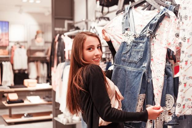 Het meisje shopaholic kiest nieuwe kleren voor de zomer