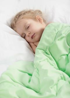 Het meisje slaapt met een deken