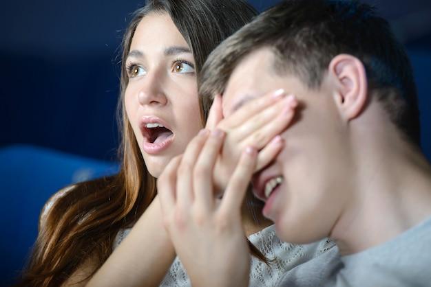 Het meisje sluit de ogen van een man in de bioscoop.