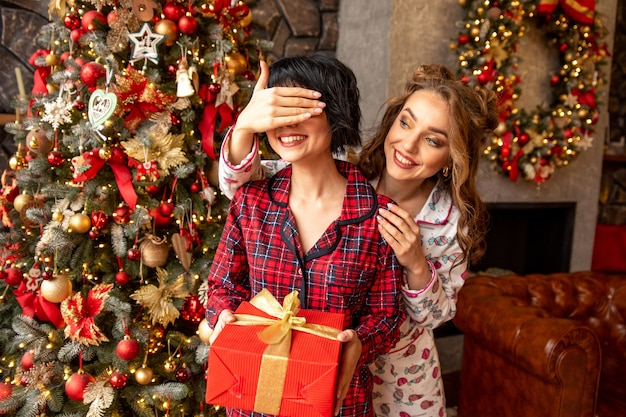 Het meisje sluit de ogen van haar vriend om haar te verrassen met een geschenk. vriendin houdt in haar handen groot rood cadeau met gouden linten. ze dragen kerstpyjama's.
