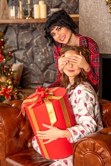 Het meisje sluit de ogen van haar vriend om haar te verrassen met een geschenk. vriendin houdt in haar handen groot rood cadeau met gouden linten.