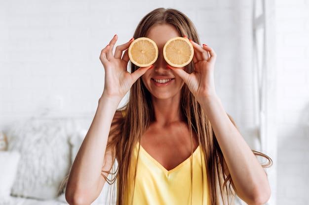 Het meisje sluit haar ogen met een citroen