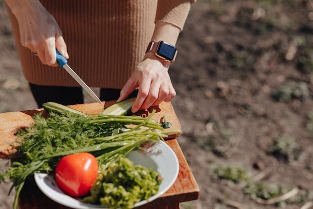 Het meisje snijdt groenten op het bord en bereidt een salade op de aard voor. zonnige dag en koken. close-up bekijken.