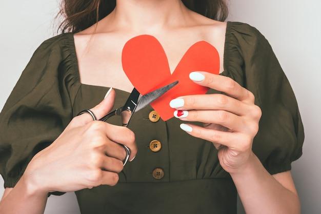 Het meisje snijdt het hart met een schaar. breuk van relaties en een gebroken hart