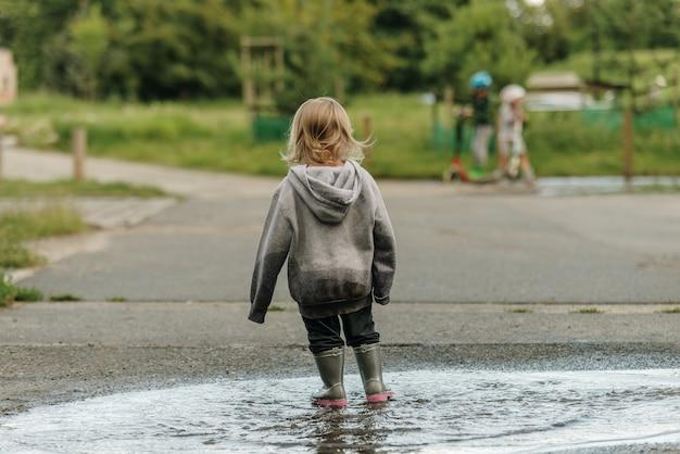 Het meisje speelt in de plas in rubberen laarzen