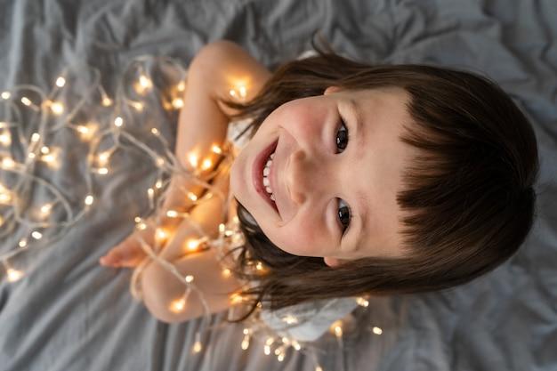 Het meisje speelt met de slingers van het nieuwjaar.