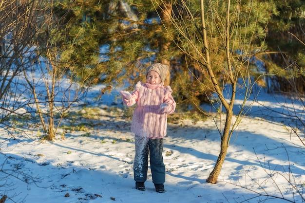 Het meisje speelt met sneeuw in de winterbos. gelukkige jeugd. winterpret vakantie concept