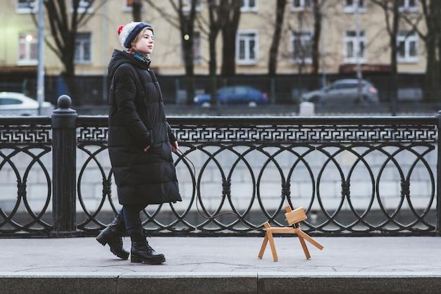 Het meisje speelt op straat met een denkbeeldige hond, die eigenlijk een lamp is