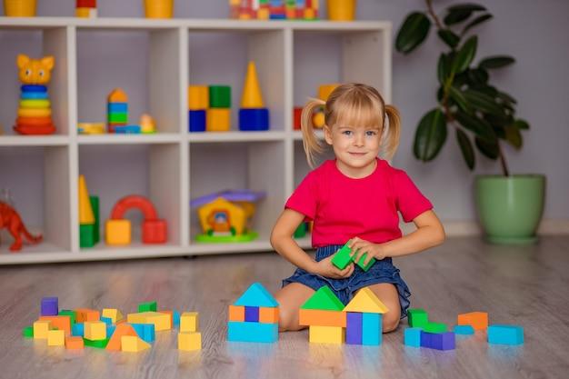 Het meisje speelt thuis, op de kleuterschool of in de kinderkamer met speelgoed. kinder ontwikkeling.