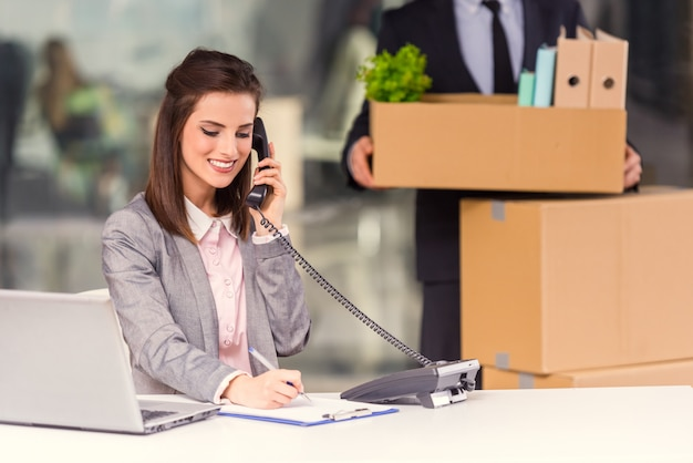 Het meisje spreekt telefonisch en werkt op de computer.