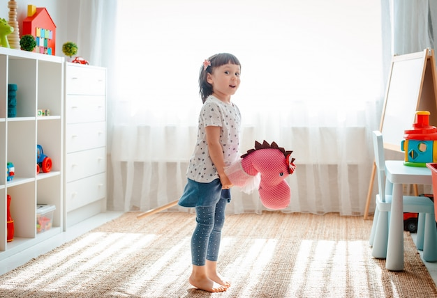 Het meisje springt en loopt op paardstok in het kinderdagverblijf.