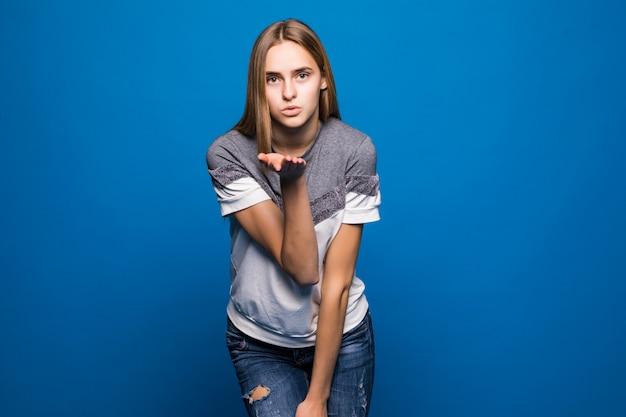 Het meisje staart in camera en blazende die luchtkus, over blauwe achtergrond wordt geïsoleerd.