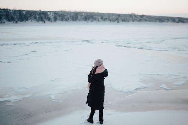 Het meisje staat alleen bij de bevroren rivier met haar rug en kijkt naar het landschap.