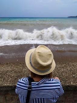 Het meisje staat bij bewolkt weer aan de kust bij de zee en kijkt in de verte