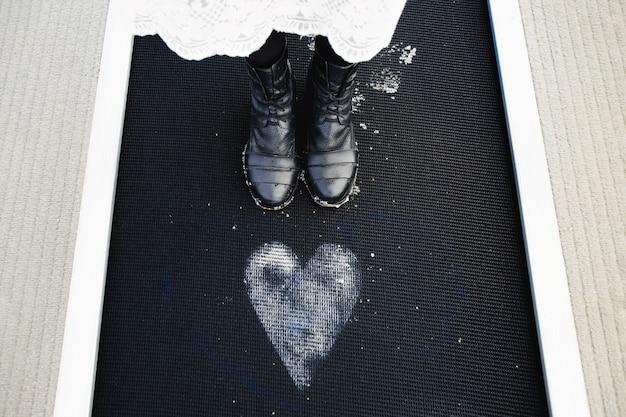 Het meisje staat in de buurt van het geschilderde hart op de vloer
