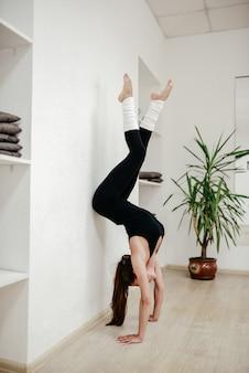 Het meisje staat in de handen van de acrobatische zaal