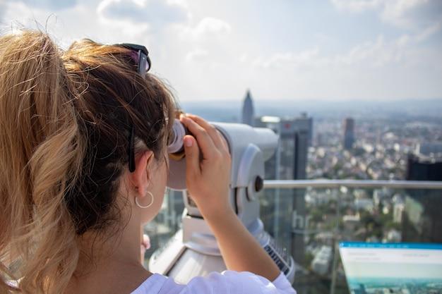 Het meisje staat op een hoge toren in de stad frankfurn on main en kijkt naar de stad