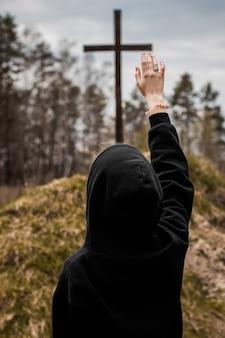 Het meisje stak haar hand op en prijst god. meisje kijkt naar het kruis. de mens gelooft in god. hoop op god