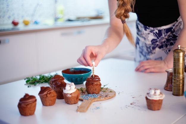 Het meisje steekt de kaars op een cupcake aan