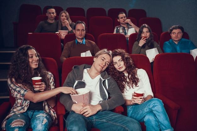 Het meisje steelt popcorn uit doos van verliefde paar.