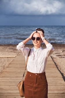 Het meisje stelt op het strand tegen het overzees.