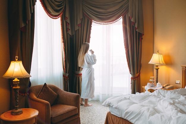 Het meisje stit bij het raam en drinkt 's ochtends koffie in de hotelkamer of thuis.