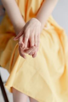 Het meisje streelt haar handen. mooie vrouwelijke handen op een gele achtergrond. zorg goed voor je handen. een zachtaardig meisje in een gele jurk.