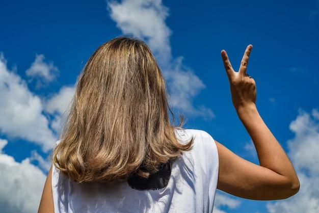 Het meisje tegen de hemel met haar rug naar de camera toont een overwinningshand