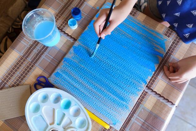Het meisje tekent blauw gouachekarton, maakt een achtergrond, zit in de huiskeuken