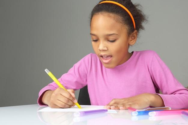 Het meisje tekent een geel potlood op wit papier
