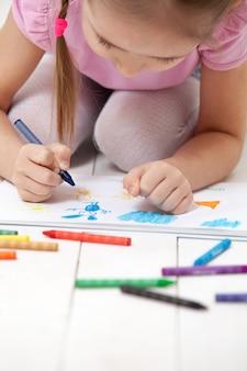 Het meisje tekent met kleurpotloden in het album