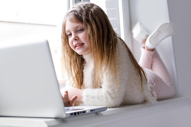 Het meisje thuis communiceert thuis op internet