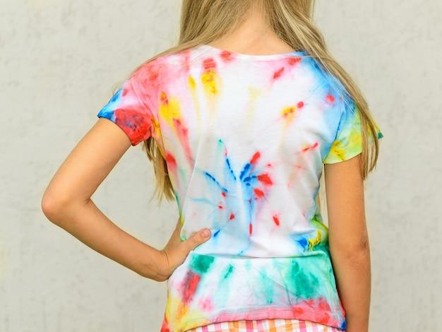 Het meisje toont de rug van een t-shirt, geschilderd in de stijl van stropdas kleurstof.