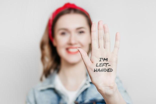 Het meisje toont haar linkerhand aan de camera en glimlacht geïsoleerd over grijze achtergrond