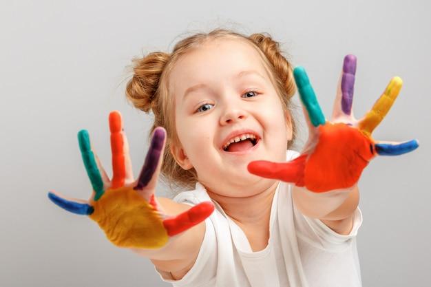 Het meisje toont handen die met verf worden geschilderd.