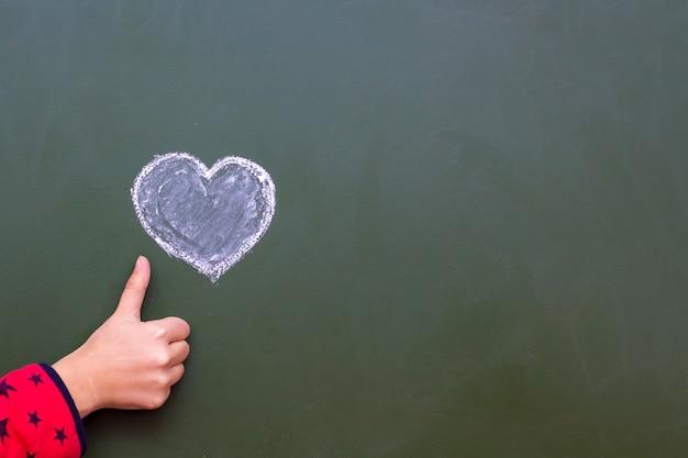 Het meisje toont ok met de hand naast het hart getekend met het krijt